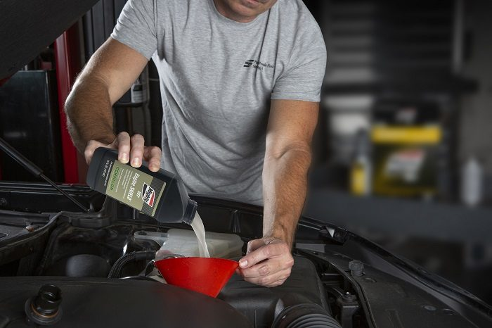 Man pouring oil in car
